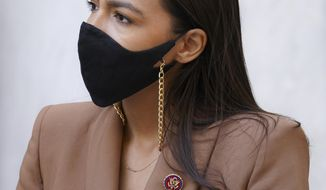 U.S. Rep. Alexandria Ocasio-Cortez, D-N.Y., wears a protective mask and a pin representing the 1116th United States Congress, her first term, as she waits to speak during a news conference outside the USPS Jamaica station, Tuesday, Aug. 18, 2020, in the Queens borough of New York. The Postal Service said it has stopped removing mailboxes and mail-sorting machines amid an outcry from lawmakers, and President Donald Trump denied he was slowing service. Democrats and some Republicans say actions by a Trump ally and a major Republican donor, new Postmaster General Louis DeJoy, have endangered millions of Americans who rely on the Postal Service for prescription drugs and other needs. (AP Photo/John Minchillo)