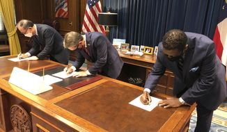 Zinus USA President Ha Bong Sung, Georgia Gov. Brian Kemp and Henry County Development Authority Chairman Pierre Clements sign papers on Tuesday, August 18, 2020 at the state Capitol in Atlanta. Zinus, a South Korean mattress and furniture maker, plans to build a $108 million factory and distribution center in McDonough, south of Atlanta. (AP Photo/Jeff Amy)