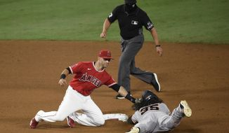 Los Angeles Angels second baseman Tommy La Stella, left, tags out San Francisco Giants' Brandon Crawford on a steal attempt during the eighth inning of a baseball game in Anaheim, Calif., Monday, Aug. 17, 2020. (AP Photo/Kelvin Kuo)