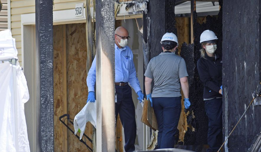 FILE - In this Aug. 5, 2020, file photo investigators examine the remnants of a house fire that killed five people in suburban Denver. Police have released a surveillance photo of three people believed to have started the fire. (AP Photo/Thomas Peipert, File)