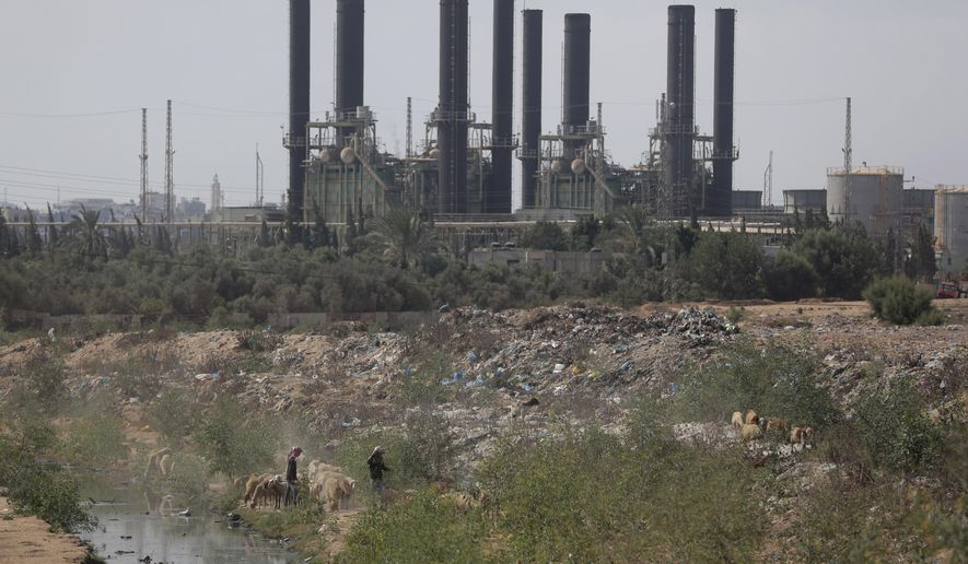 Palestinian shepherds walk with their sheep in front of Gaza's power plant after it was shutdown according to Gaza's Hamas officials, in the town of Nusairat, central Gaza Strip, Tuesday, Aug. 18, 2020.(AP Photo/ Khalil Hamra)