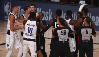 Officials separate the Dallas Mavericks and the Los Angeles Clippers after the teams got into a scuffle in Game 1 of an NBA basketball first-round playoff series, Monday, Aug. 17, 2020, in Lake Buena Vista, Fla. (Kim Klement/Pool Photo via AP)