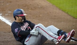 Washington Nationals' Kurt Suzuki falls to the ground while at-bat in the third inning during a baseball game against the Atlanta Braves on Tuesday, Aug. 18, 2020, in Atlanta. (AP Photo/Brynn Anderson)