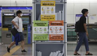 People wearing face masks pass by posters about precautions against the coronavirus at a subway station in Seoul, South Korea, Tuesday, Aug. 18, 2020. (AP Photo/Ahn Young-joon)