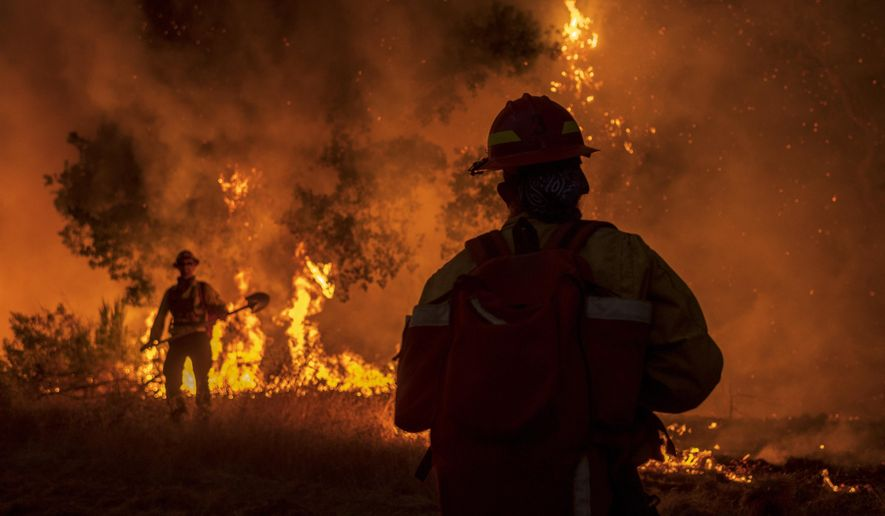 Members of the Grizzly Firefighters fight the Carmel Fire near Carmel Valley, Calif., Tuesday, Aug. 18, 2020. (AP Photo/Nic Coury)