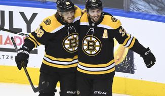 Boston Bruins' Patrice Bergeron (37) celebrates his goal with teammate David Pastrnak (88) during second period of an NHL Stanley Cup playoff hockey game against the Carolina Hurricanes in Toronto on Wednesday, Aug. 19, 2020. (Nathan Denette/The Canadian Press via AP)