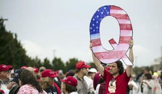 In this Aug. 2, 2018, file photo, a protester holds a Q sign waits in line with others to enter a campaign rally with President Donald Trump in Wilkes-Barre, Pa. (AP Photo/Matt Rourke, File)