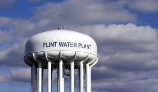 In this March 21, 2016, file photo, the Flint Water Plant water tower is seen in Flint, Mich. Multiple news outlets report Wednesday, Aug. 19, 2020, that the state of Michigan has reached a $600 million agreement to compensate Flint residents whose health was damaged by lead-tainted drinking water. (AP Photo/Carlos Osorio, File)