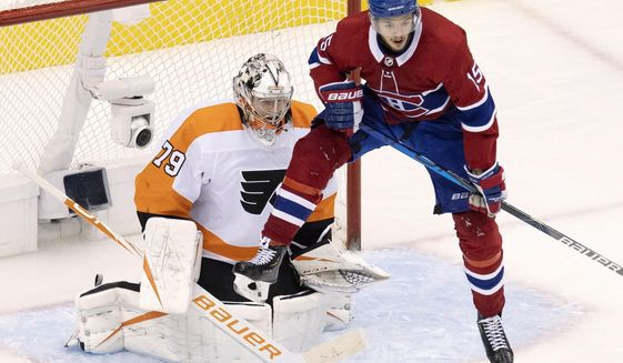 Montreal Canadiens centre Jesperi Kotkaniemi (15) leaps to try to deflect a shot in front of Philadelphia Flyers goaltender Carter Hart (79) during third period NHL Eastern Conference Stanley Cup first round playoff hockey action in Toronto, Tuesday, Aug. 18, 2020. (Frank Gunn/The Canadian Press via AP)