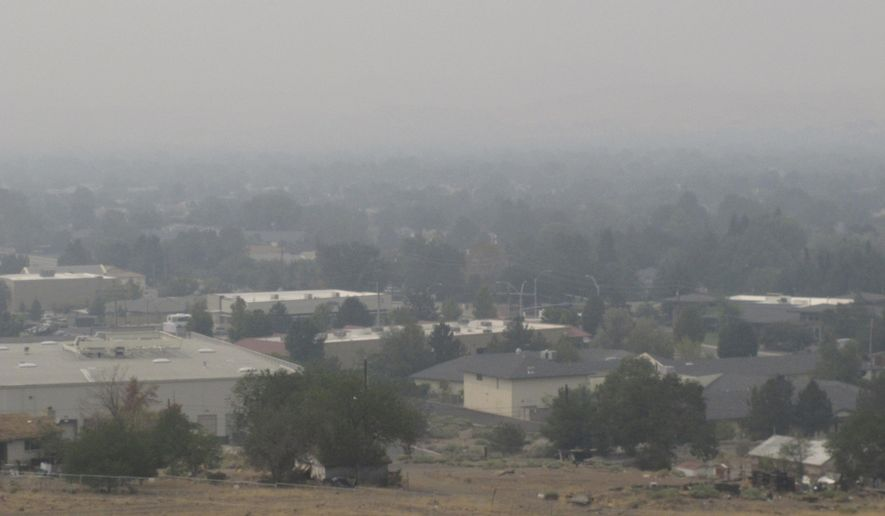 """Smoke from California wildfires up to 200 miles away blankets a residential neighborhood in Sparks, Nev., Wednesday, Aug. 19, 2020. Local schools canceled all outdoor activities as the air quality index approached the """"very unhealthy"""" category for the general population Wednesday afternoon. (AP Photo/Scott Sonner)"""