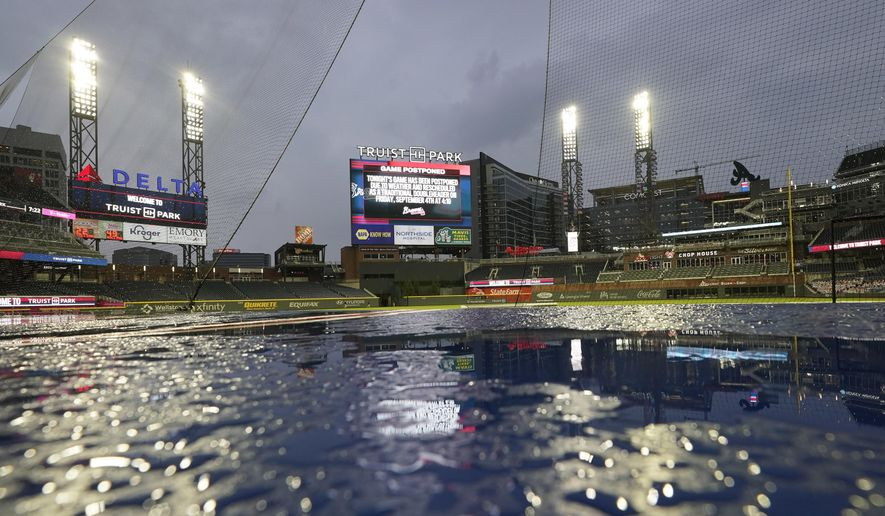A sign over centerfield at Truist Park announces that a baseball game between the Atlanta Braves and the Washington Nationals has been postponed because of rain Wednesday, Aug. 19, 2020, in Atlanta. (AP Photo/John Bazemore)