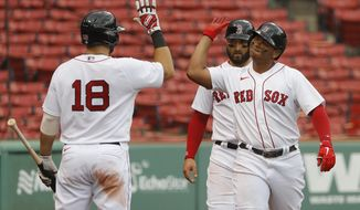 Boston Red Sox's Rafael Devers is congratulated by Mitch Moreland (18) after his two-run home run against the Philadelphia Phillies during the third inning of a baseball game Wednesday, Aug. 19, 2020, at Fenway Park in Boston. (AP Photo/Winslow Townson)