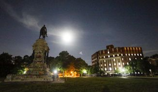FILE - This Friday June 6, 2020 file photo shows the Moon as it illuminates the statue of Confederate General Robert E. Lee on Monument Avenue in Richmond, Va. When the bronze equestrian statue of Gen. Robert E. Lee arrived by rail in Richmond from Paris in 1890, it took 10,000 men, women and children to haul its pieces more than a mile to the site where the towering monument was erected as a tribute to a Confederate hero. Now, 130 years later, the challenges of removing the statue are more related to the intricate logistics of disassembling and transporting it to a storage facility, as well as ensuring worker safety amid heated public debate about Southern heritage versus racism. (AP Photo/Steve Helber)