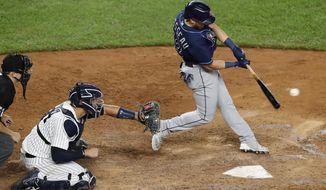 Tampa Bay Rays pinch hitter Michael Brosseau hits an RBI single during the eighth inning of a baseball game against the New York Yankees, Wednesday, Aug. 19, 2020, in New York. Yankees catcher Gary Sanchez (24) and home plate umpire Jansen Visconti are behind the plate. (AP Photo/Kathy Willens)