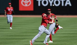Cincinnati Reds' Mike Moustakas, front, catches a fly ball in front of Nicholas Castellanos, back, in an intrasquad game during team baseball practice at Great American Ball Park in Cincinnati, Wednesday, July 8, 2020. (AP Photo/Aaron Doster)