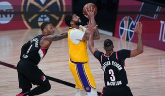 Los Angeles Lakers forward Anthony Davis goes to the basket between Portland Trail Blazers guard Damian Lillard (0) and guard CJ McCollum (3) during the second half of an NBA basketball game Tuesday, Aug. 18, 2020, in Lake Buena Vista, Fla. (AP Photo/Ashley Landis, Pool)