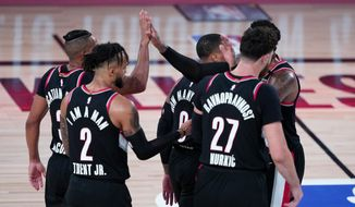 The Portland Trail Blazers celebrate after defeating the Los Angeles Lakers in an NBA basketball game Tuesday, Aug. 18, 2020, in Lake Buena Vista, Fla. Portland won 100-93. (AP Photo/Ashley Landis, Pool)