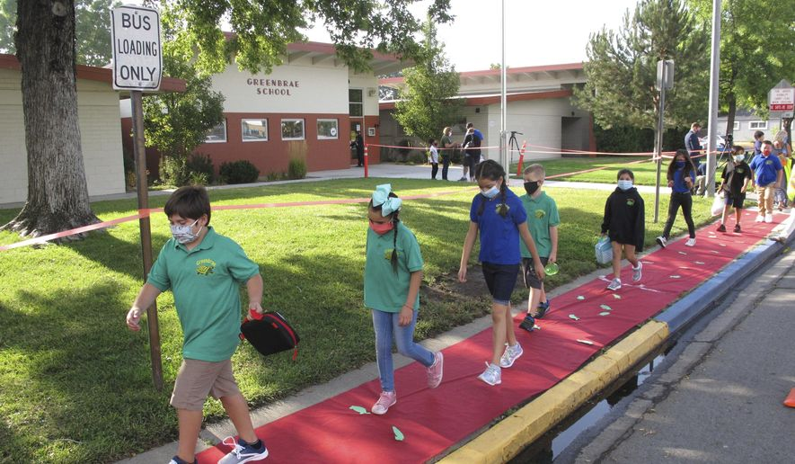 Students return to Greenbrae Elementary School in Sparks, Nev., on Tuesday, Aug. 18, 2020, for the first time since March with mandatory masks and social distancing to help guard against the spread of the coronavirus. Washoe County schools are using a combination of classroom instruction and distance learning. Nevada's largest school district resumes school in Las Vegas next week using strictly remote learning. (AP Photo/Scott Sonner).