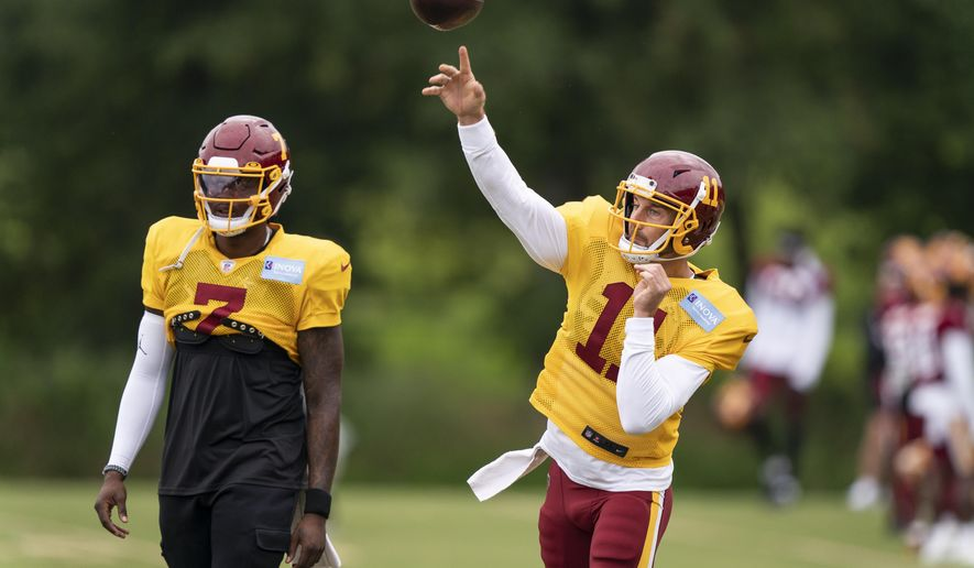 Washington quarterback Alex Smith, right, throws with quarterback Dwayne Haskins Jr., standing nearby, during practice at the team's NFL football training facility, Wednesday, Aug. 19, 2020, in Ashburn, Va. (AP Photo/Alex Brandon)