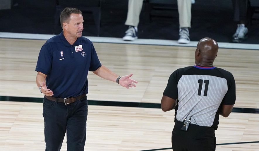 Washington Wizards head coach Scott Brooks talks with referee Derrick Collins (11) during the second half of an NBA basketball game between the Boston Celtics and the Washington Wizards Thursday, Aug. 13, 2020 in Lake Buena Vista, Fla. (AP Photo/Ashley Landis, Pool)  **FILE**
