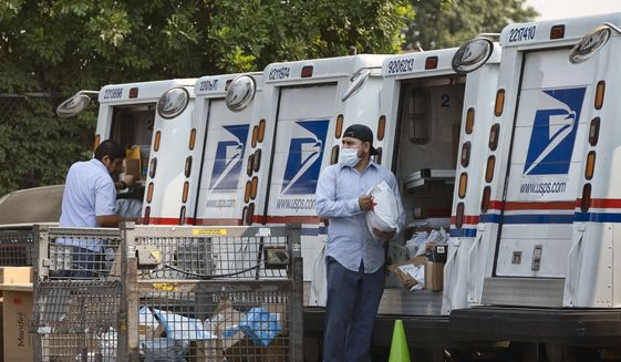 In this file photo, postal workers load packages in their mail delivery vehicles at the Panorama City Post Office on Thursday, Aug. 20, 2020, in the Panorama City section of Los Angeles. (AP Photo/Richard Vogel)  **FILE**
