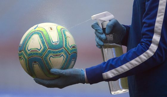 A ball catcher wearing plastic gloves amid the new coronavirus pandemic, disinfects the ball during a local championship soccer match between Nacional and Penarol in Montevideo, Uruguay, Sunday, Aug. 9, 2020. (AP Photo/Matilde Campodonico)