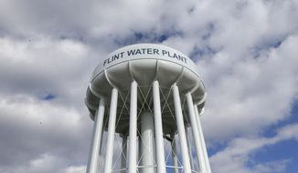 FILE - In this March 21, 2016, file photo, the Flint Water Plant water tower is seen in Flint, Mich. Michigan Gov. Gretchen Whitmer says a proposed $600 million deal between the state of Michigan and Flint residents harmed by lead-tainted water is a step toward making amends. Officials announced the settlement Thursday, Aug. 20, 2020, which must be approved by a federal judge. (AP Photo/Carlos Osorio, File)