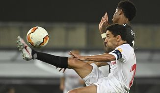 Sevilla's Jesus Navas, left. clears the ball under pressure from Manchester United's Marcus Rashford during the Europa League semifinal soccer match between Sevilla and Manchester United in Cologne, Germany, Sunday, Aug. 16, 2020. (Ina Fassbender/Pool Via AP)