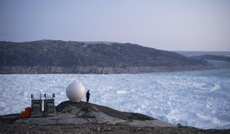 FILE - In this Aug. 16, 2019 file photo, a woman stands next to an antenna at an NYU base camp at the Helheim glacier in Greenland. According to a study released on Thursday, Aug. 20, 2020, Greenland lost a record amount of ice during an extra warm 2019, with the melt massive enough to cover California in more than four feet (1.25 meters) of water. (AP Photo/Felipe Dana)