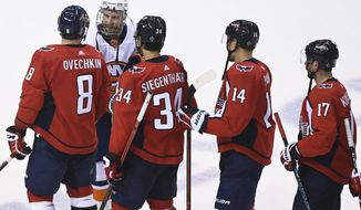 Washington Capitals left wing Alex Ovechkin (8) shakes hands with New York Islanders right wing Leo Komarov (47) after the Capitals were eliminated after an NHL Stanley Cup playoff hockey game in Toronto on Thursday, Aug. 20, 2020. (Nathan Denette/The Canadian Press via AP)