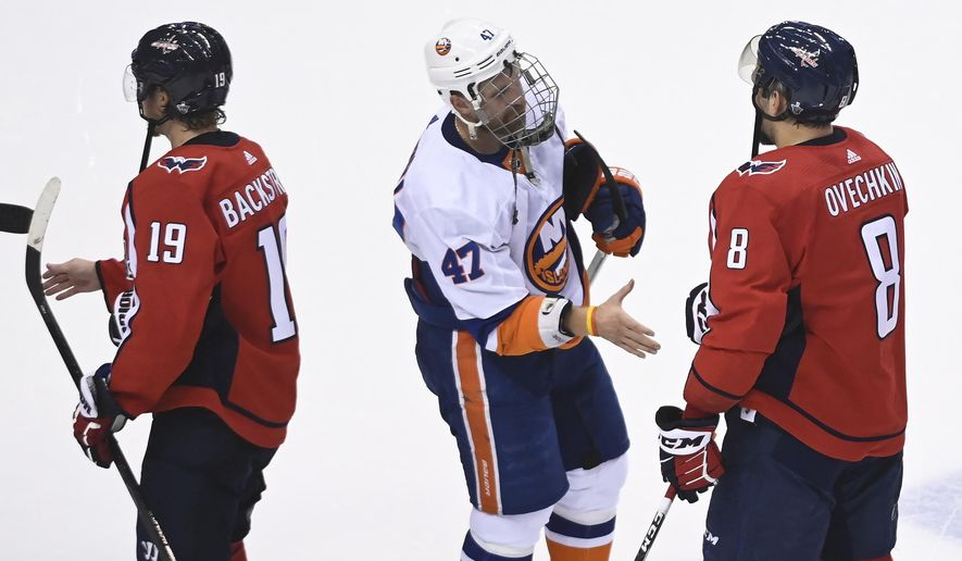 Washington Capitals left wing Alex Ovechkin (8) shakes hands with New York Islanders right wing Leo Komarov (47) after an NHL Stanley Cup playoff hockey game in Toronto on Thursday, Aug. 20, 2020. (Nathan Denette/The Canadian Press via AP)