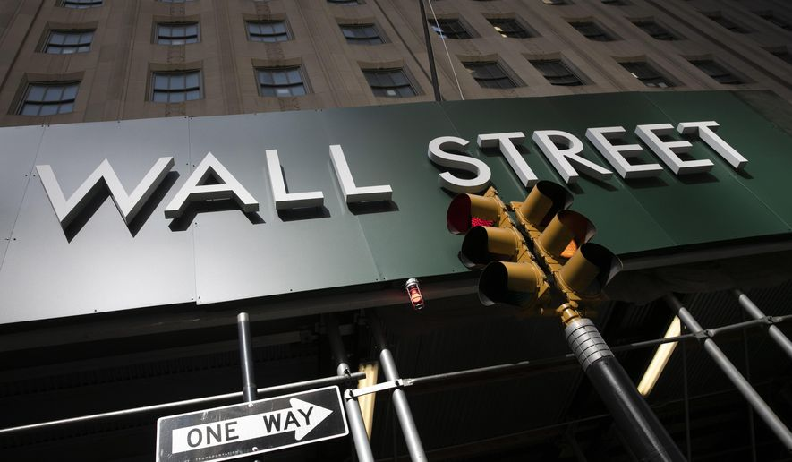 FILE - In this June 16, 2020, file photo, a sign for a Wall Street building is shown in New York. This earnings reporting season for big U.S. companies has been historically bad, and yet still much better than Wall Street expected. (AP Photo/Mark Lennihan, File)