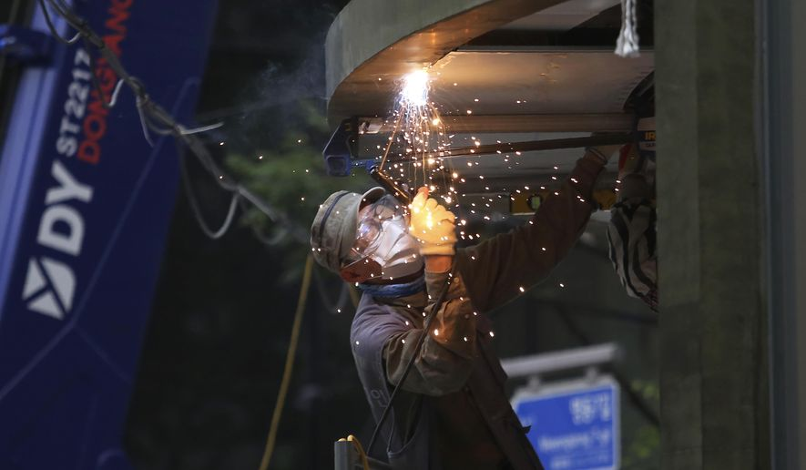 A worker wearing a face mask to help protect against the spread of the coronavirus welds at a construction site in Seoul, South Korea, Friday, Aug. 21, 2020. (AP Photo/Ahn Young-joon)