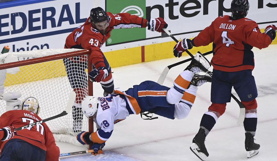 New York Islanders left wing Anthony Beauvillier (18) hits his head into the post after scoring on Washington Capitals goaltender Braden Holtby (70) as Capitals right wing Tom Wilson (43) and defenceman Brenden Dillon (4) look on during the second period period of an NHL Stanley Cup playoff hockey game in Toronto on Thursday, Aug. 20, 2020. (Nathan Denette/The Canadian Press via AP)