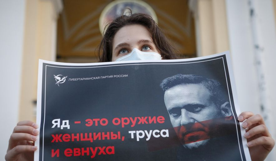 """A protester stands holds a poster reads """"poison is the weapon of a woman, a coward and a eunuch!"""" during a picket in support of Russian opposition leader Alexei Navalny in the center of St. Petersburg, Russia, Thursday, Aug. 20, 2020. Russian opposition politician Alexei Navalny is on a hospital ventilator in a coma, after falling ill from a suspected poisoning, according to his spokeswoman Kira Yarmysh. (AP Photo/Elena Ignatyeva)"""