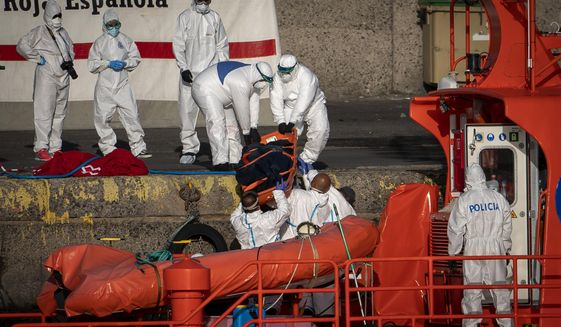 Emergency services carry a dead body of a migrant rescued by the Spanish Maritime Rescue Service, at the Arguineguin port in Gran Canaria island, Spain, Friday, Aug. 21, 2020. Spanish authorities say that five migrants have died and 11 survived while trying to reach the southern Canaries Islands, bringing to 20 the number of people who have lost their lives this week in the perilous migration route to Europe. (AP Photo/Emilio Morenatti)