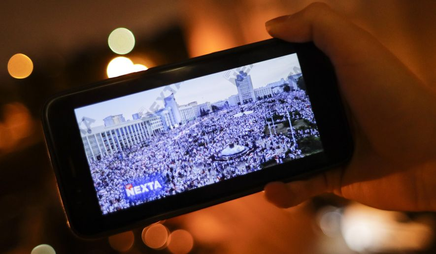 A man looks at Telegram channel NEXTA Live on his smartphone in Minsk, Belarus, Wednesday, Aug. 19, 2020. The Telegram messaging app has become an indispensable tool in coordinating the unprecedented mass protests that have rocked Belarus since Aug. 9, when election officials announced President Alexander Lukashenko had won a landslide victory to extend his 26-year rule in a vote widely seen as rigged. (AP Photo/Sergei Grits)