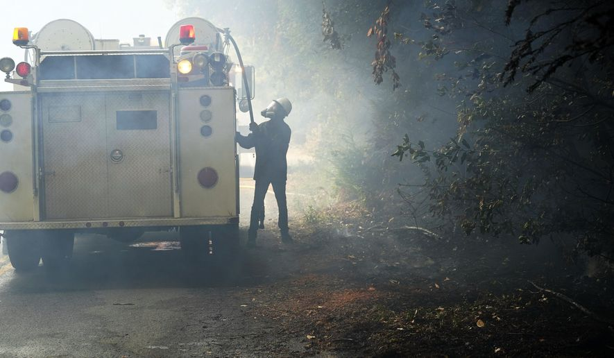 Jesse Katz pulls a hose from a vehicle carrying water while volunteering to fight the CZU August Lightning Complex Fire on Friday, Aug. 21, 2020, in Bonny Doon, Calif. Wildfires that have forced tens of thousands of people from their homes are still raging in California. (AP Photo/Marcio Jose Sanchez)