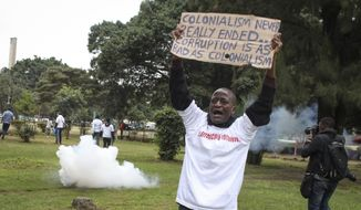 Demonstrators run from teargas fired by police at a protest against alleged corruption, including the theft of supplies for the fight against the coronavirus, at Uhuru Park in downtown Nairobi, Kenya Friday, Aug. 21, 2020. Kenya's police teargassed and arrested some of the protesters who were holding a peaceful demonstration following the announcement that the country's anti-corruption agency is investigating the theft of millions of dollars of supplies from the Kenya Medical Supplies Authority. (AP Photo)