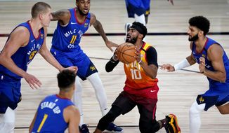 Utah Jazz's Mike Conley (10) drives as Denver Nuggets' Monte Morris (11), Nikola Jokic (15), Michael Porter Jr. (1) and Jamal Murray, right, defend during the first half of an NBA basketball first round playoff game Friday, Aug. 21, 2020, in Lake Buena Vista, Fla. (AP Photo/Ashley Landis, Pool)