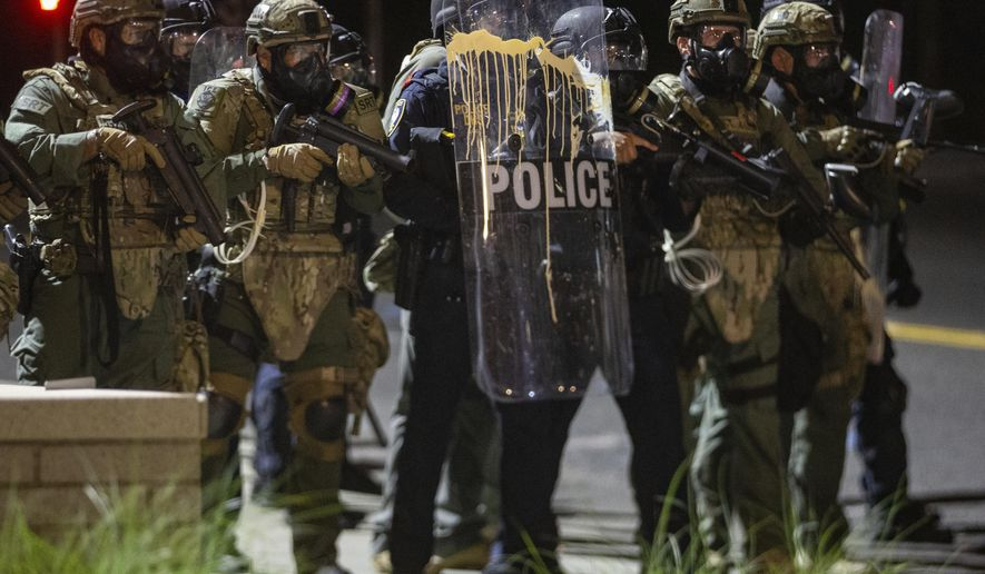 In this file photo, police confront protesters outside the U.S. Immigration and Customs Enforcement office in  Portland, Ore., Thursday, Aug. 20, 2020.  Portland police say people in a group of about 100 late Thursday and early Friday sprayed the building with graffiti, hurled rocks and bottles at agents and shined laser lights at them.(Mark Graves /The Oregonian via AP)  **FILE**