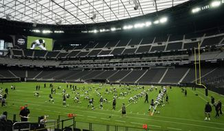 Las Vegas Raiders players stretch during an NFL football training camp practice at Allegiant Stadium, Friday, Aug. 21, 2020, in Las Vegas. (AP Photo/John Locher)