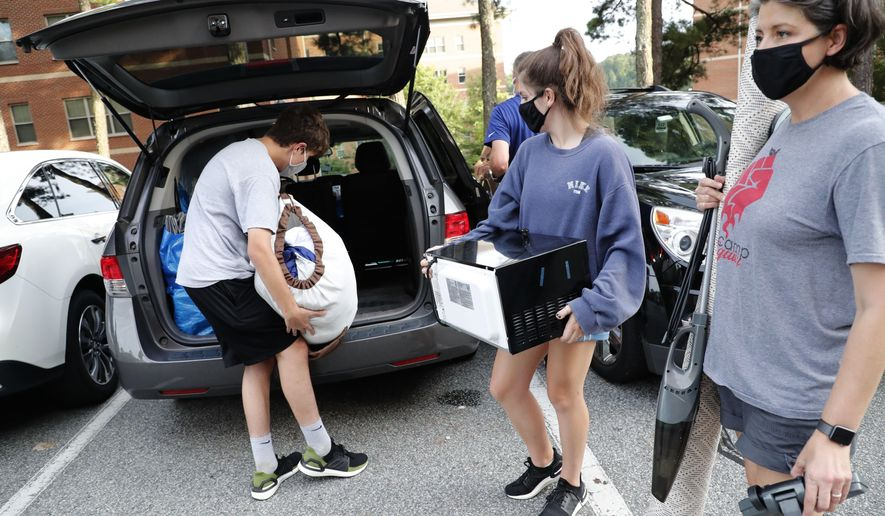 Miranda Darwin, from Raleigh and a freshman at UNC-Chapel Hill, center, gets help from her brother, Sam, and her mother Stacy while moving out of her room at Hinton James residence hall, Tuesday, Aug. 18, 2020, in Chapel Hill, N.C. (Ethan Hyman/The News & Observer via AP)  **FILE**