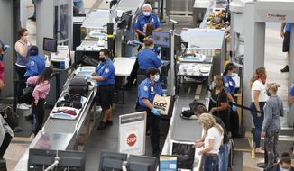 Transportation Security Administration agents process passengers at the south security checkpoint in Denver International Airport Wednesday, June 10, 2020, in Denver, as travelers deal with the effects of the new coronavirus. (AP Photo/David Zalubowski)