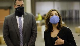 Oklahoma State Superintendent of Public Instruction Joy Hofmeister, right, answers a question at the Central Oklahoma PPE distribution warehouse where supplies for schools are being distributed Tuesday, Aug. 18, 2020, in Oklahoma City. Listening at left is Oklahoma Gov. Kevin Stitt.(AP Photo/Sue Ogrocki)
