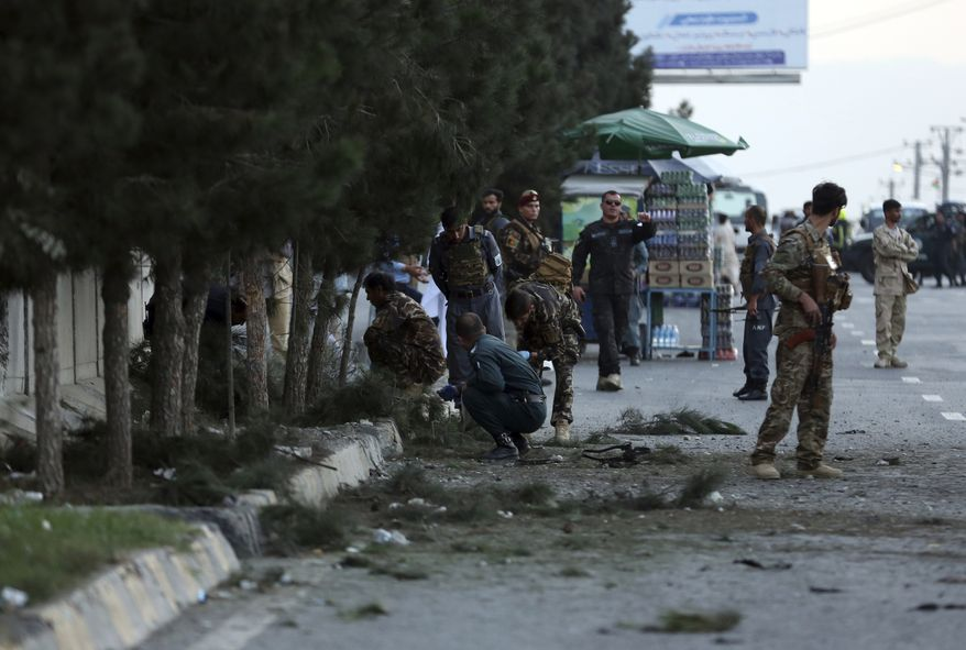 Afghan security personnel inspect site of a roadside bomb explosion in Kabul, Afghanistan, Saturday, Aug. 22, 2020. (AP Photo/Mariam Zuhaib)