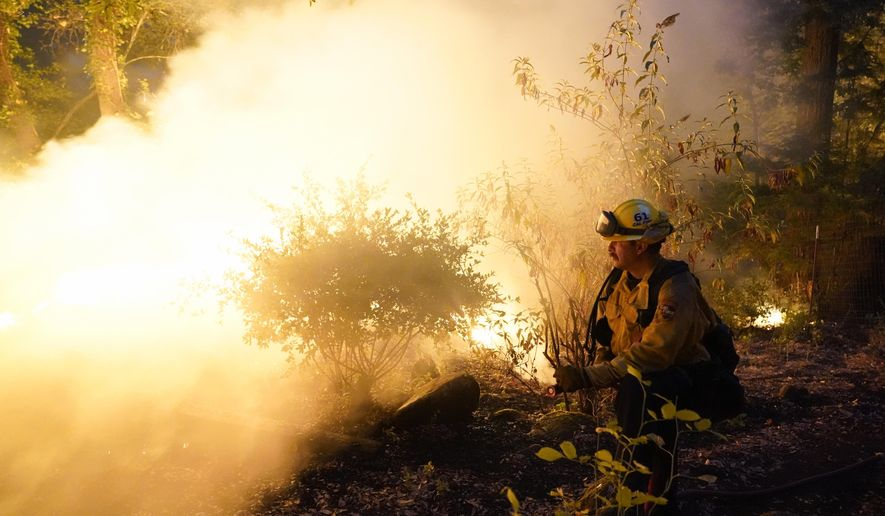 Firefighter Jeremy Damon of the Nevada Yuba Placer Fire Dept. monitors a controlled burn in the backyard of a home in front of the advancing CZU August Lightning Complex Fire Friday, Aug. 21, 2020, in Boulder Creek, Calif. (AP Photo/Marcio Jose Sanchez)