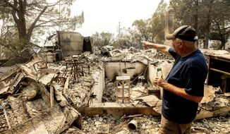 Hank Hanson, 81, gestures to the kitchen of his home, destroyed by the LNU Lightning Complex fires, in Vacaville, Calif., on Friday, Aug. 21, 2020. Hanson, who built the house thirty years ago, does not think he will rebuild. (AP Photo/Noah Berger)