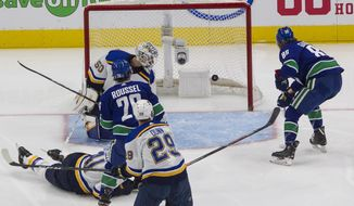 Vancouver Canucks' Antoine Roussel (26) scores against St. Louis Blues goalie Jordan Binnington (50) during second-period NHL Western Conference Stanley Cup playoff hockey game action in Edmonton, Alberta, Friday, Aug. 21, 2020. (Jason Franson/The Canadian Press via AP)