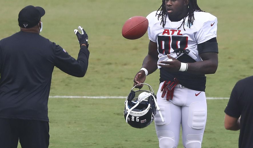 Atlanta Falcons defensive end Takk McKinley takes the field and a football during an NFL training camp football practice Saturday, Aug. 22, 2020, in Flowery Branch, Ga. (Curtis Compton/Atlanta Journal-Constitution via AP, Pool)